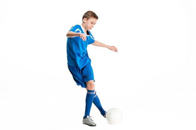 Jeune garçon avec un ballon de soccer faisant voler coup de pied