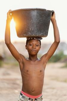 Jeune garçon avec bassin sur la tête
