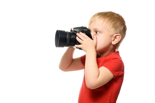 Jeune garçon blond avec appareil photo. portrait, isolé sur fond blanc. vue de côté.