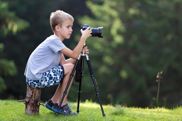 Jeune garçon blond assis sur une souche prenant une photo
