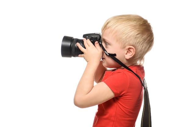 Jeune garçon blond en chemise rouge avec appareil photo. portrait, isolé sur fond blanc
