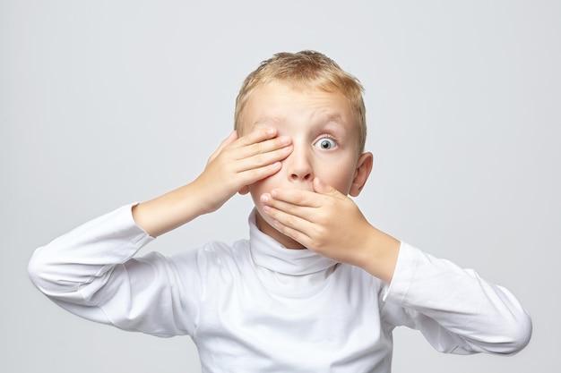 Jeune garçon blond couvre sa bouche et un œil avec sa main