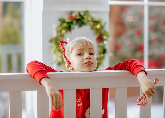 Jeune garçon blond en pyjama d'hiver rouge et bandeau posant près de lit blanc