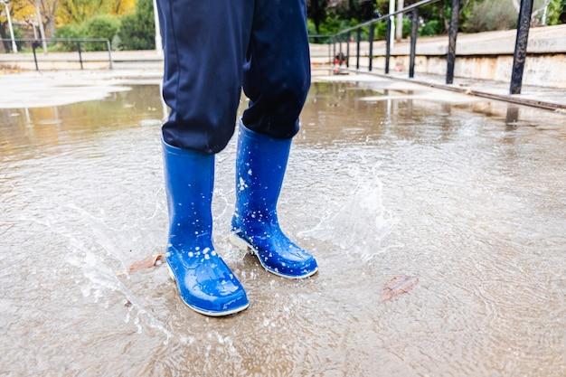 Jeune garçon avec des bottes en caoutchouc bleu saute par-dessus une flaque d'eau dans un parc de sa ville.