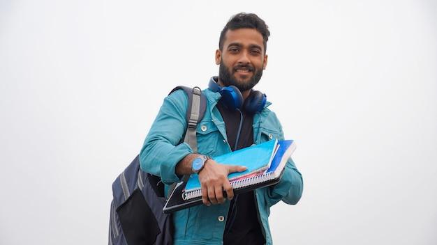 Jeune garçon avec des cahiers sur blanc