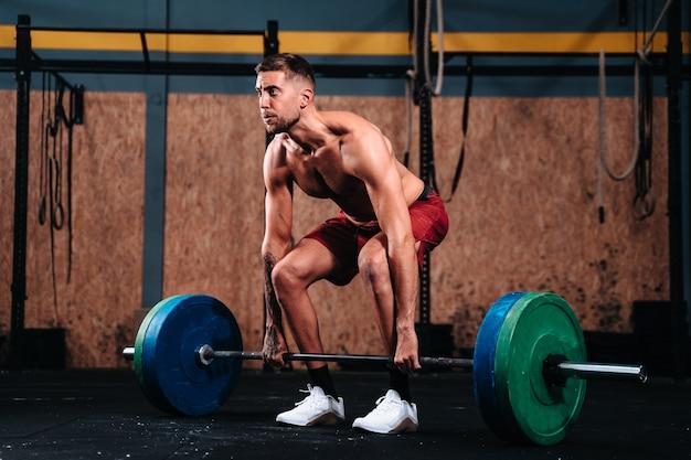 Jeune garçon caucasien dans ses 30s fitness soulevant le soulevé de terre