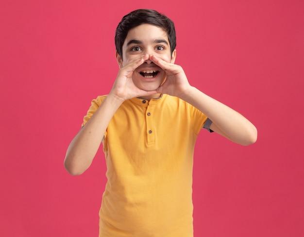 Jeune garçon caucasien impressionné gardant les mains autour de la bouche en chuchotant