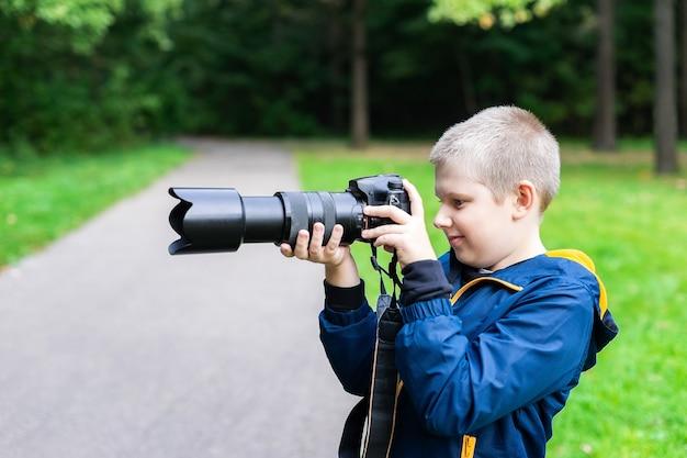 Jeune garçon caucasien prenant une photo avec son appareil photo reflex numérique. nature ambiante.