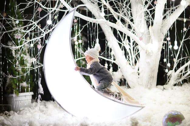 Jeune garçon en chapeau d'hiver, pull et écharpe escalade la grande lune blanche jouet dans une forêt magique avec grand arbre blanc.