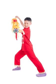 Jeune garçon chinois en robe traditionnelle de couleur rouge jouant marionnette lion chinois sur fond blanc