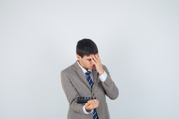 Jeune garçon en costume formel tenant la calculatrice, tenant la main sur le front et à la vue ennuyée, de face.
