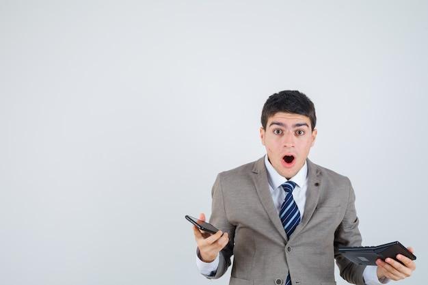 Jeune garçon en costume formel tenant le téléphone et la calculatrice et l'air surpris, vue de face.