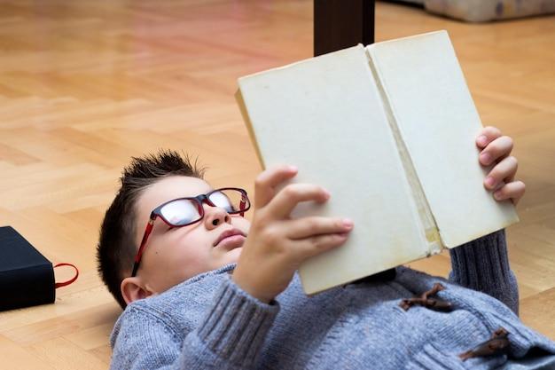 Jeune Garçon Couché Sur Le Sol Parmi Les Livres Et En Lisant Un Livre, Boy étudie Ses Devoirs. Photo gratuit