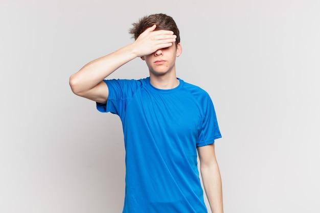 Jeune garçon couvrant les yeux d'une main se sentant effrayé ou anxieux, se demandant ou attendant aveuglément une surprise