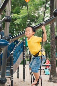Jeune garçon dans le parc d'escalade
