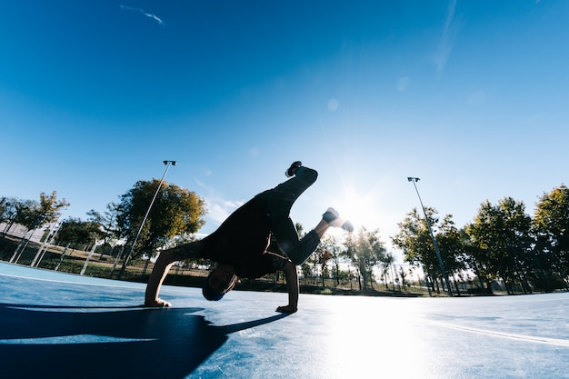 Jeune garçon dansant et posant au terrain de basket