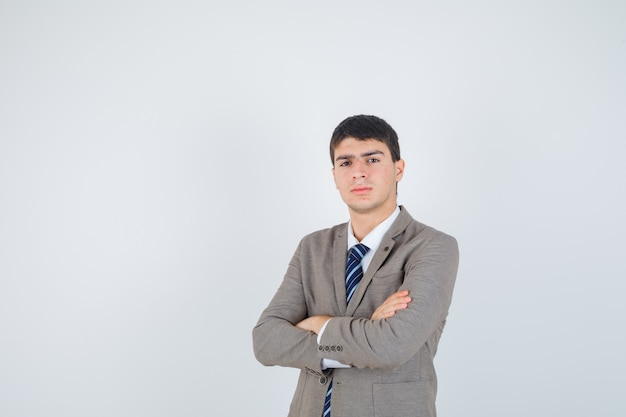 Jeune garçon debout les bras croisés en costume formel et à la vue de face, confiant.