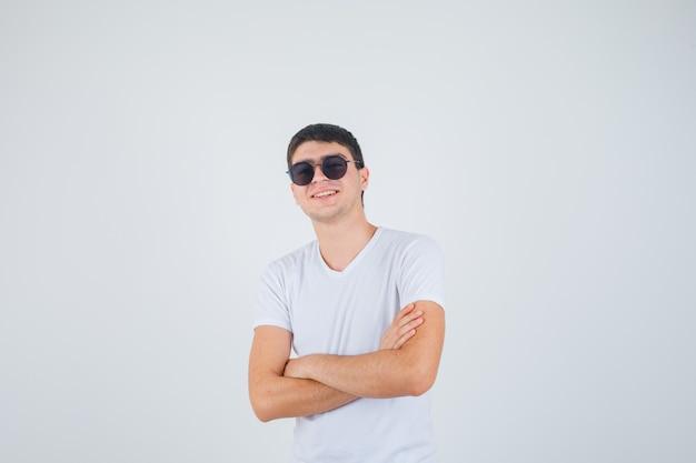 Jeune garçon debout avec les bras croisés en t-shirt et à la joyeuse, vue de face.