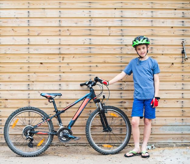 Jeune garçon debout avec son vélo