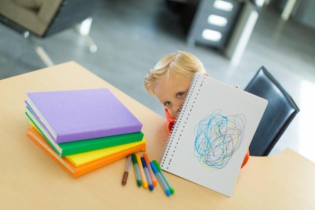 Jeune garçon dessine au bureau