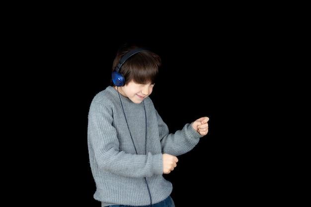 Jeune garçon écoutant de la musique sur le lecteur avec des écouteurs sur fond noir