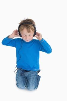 Jeune garçon écoute de la musique à travers des écouteurs