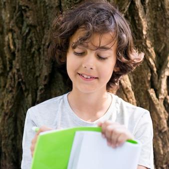 Jeune garçon écrit en plein air