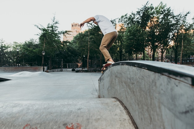 Jeune garçon effectuant des tours avec la planche à roulettes dans un skate park