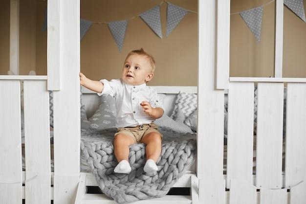 Jeune garçon enfant dans une chemise blanche et un short beige souriant et regardant de côté en position assise