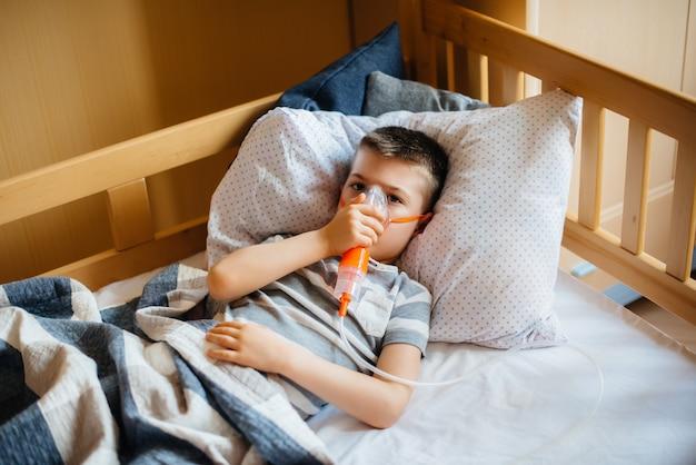 Un jeune garçon est inhalé lors d'une maladie pulmonaire. covid19, coronavirus, pandémie.