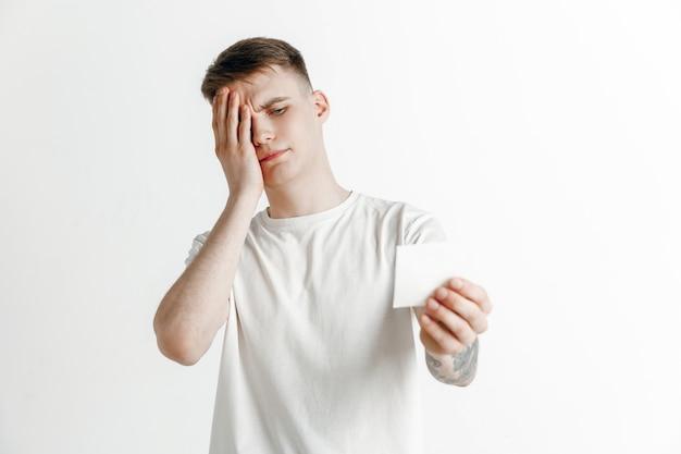 Jeune garçon avec une expression d'échec malheureux surpris pari sur fond de studio. émotions faciales humaines et concept de pari.
