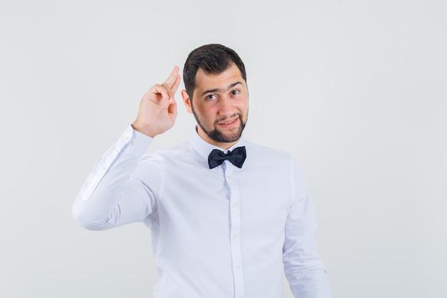 Jeune garçon faisant des gestes avec deux doigts en chemise blanche et à la gaieté. vue de face.