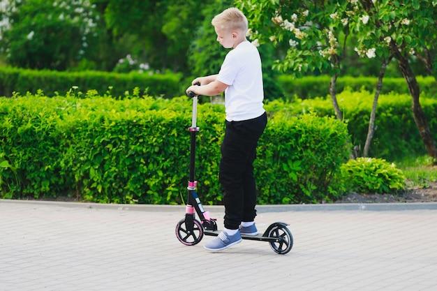 Un jeune garçon fait du scooter dans le parc en été. photo de haute qualité