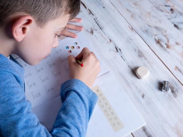 Jeune garçon fait ses devoirs, concept d'enseignement à domicile