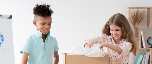 Jeune garçon et fille apprenant à recycler