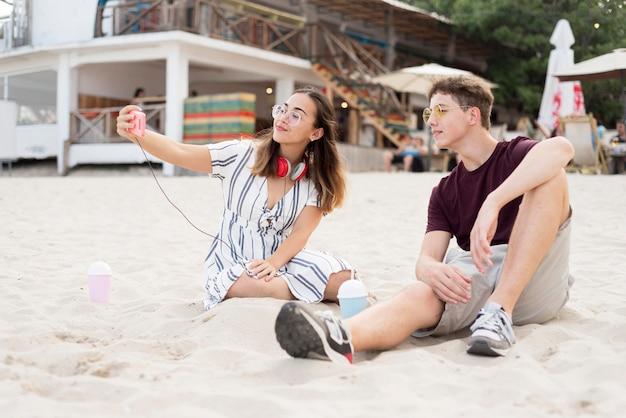 Jeune garçon et fille se détendre ensemble à la plage
