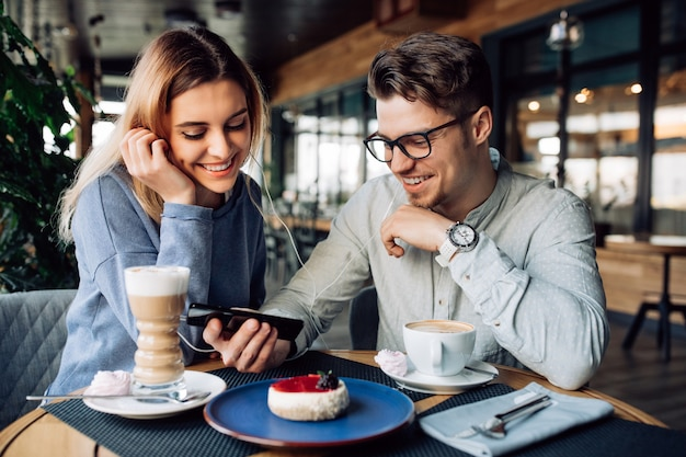 Jeune garçon gai et une fille dans les écouteurs, regarder un film sur téléphone mobile