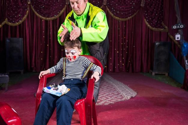 Jeune garçon habillé en clown assis sur une chaise avec plateau de maquillage sur les genoux sur scène, homme portant une veste brillante avec les mains positionnées sur la tête du garçon
