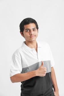 Jeune garçon indien abandonnant le pouce sur le mur blanc