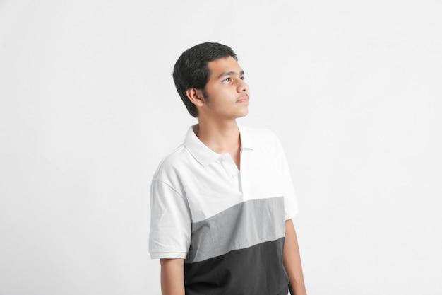 Jeune garçon indien à côté sur mur blanc