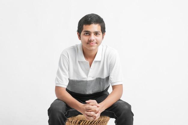 Jeune garçon indien montrant l'expression sur le mur blanc
