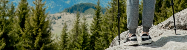 Jeune garçon insouciant escaladant d'énormes rochers solides, utilisant des poteaux pour atteindre facilement le sommet, profitant de la vue sur les merveilles naturelles en chemin