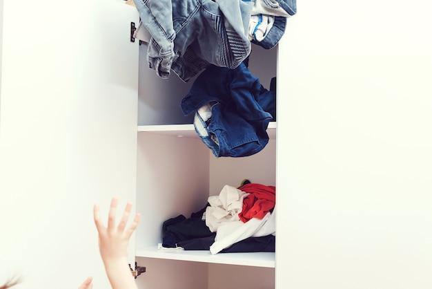 Jeune garçon jetant des vêtements sales dans le placard. mess dans la garde-robe et le dressing. armoire à vêtements désordonnée en désordre. chambre d'enfant à la maison en désordre.