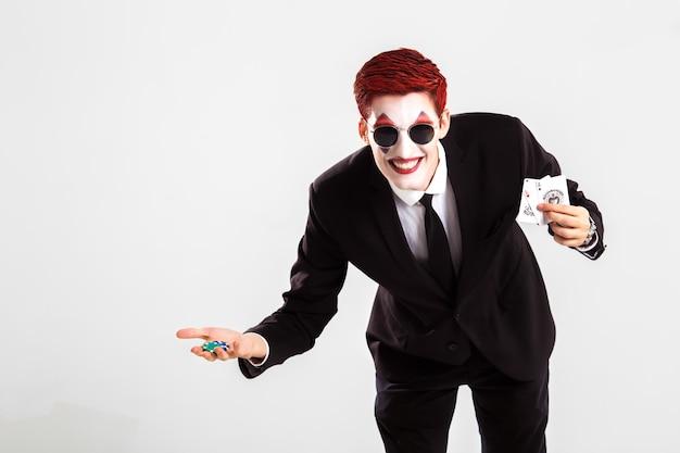 Un jeune garçon avec un joker maquillage artistique. concept de jeu et de casino. tourné en studio. fond blanc .