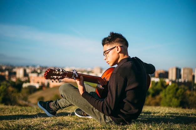 Jeune garçon jouant de la guitare dans la ville de madrid, espagne en arrière-plan.