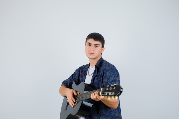 Jeune garçon jouant de la guitare tout en regardant la caméra en t-shirt et à la vue de face, confiant.