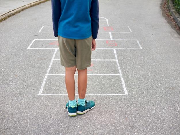 Jeune garçon jouant à la marelle à l'extérieur