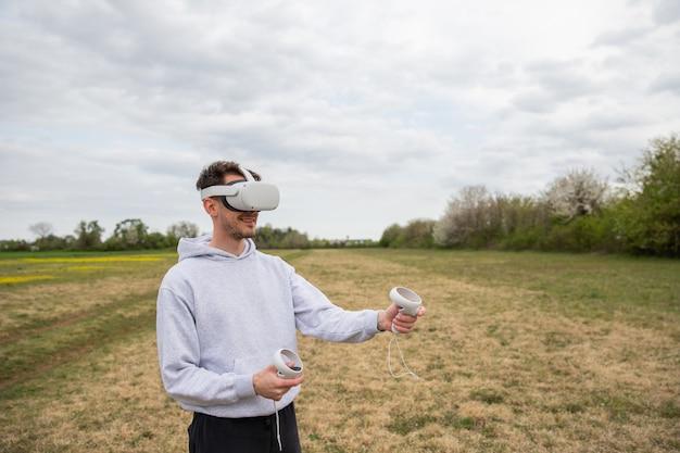 Un jeune garçon joue avec son casque vr et ses contrôleurs dans une pelouse dans un parc en plein air.