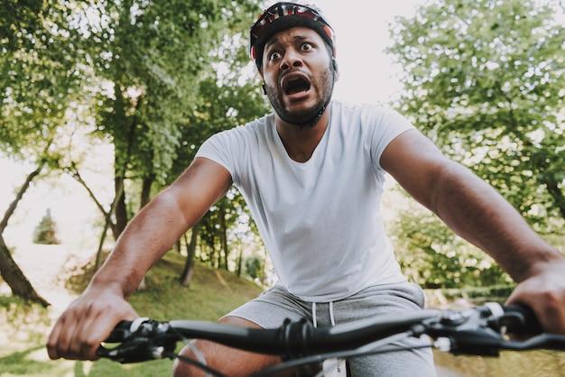 Jeune garçon latin effrayé fait du vélo dans le parc.