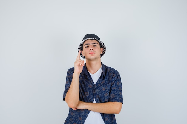 Jeune garçon levant l'index en geste eureka tout en tenant la main sous le coude en t-shirt blanc, chemise à fleurs, casquette et à la recherche sensible. vue de face.